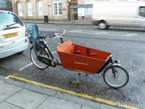 Long cargo bike spotted in Glasgow. Note the brackets for a front seat, which, with the rear seat, means this Bakfiets could have five on board not including the captain.